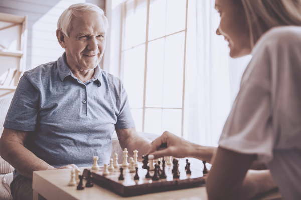 Man in a hospice playing chess and still retaining a quality of life. Hospice recruitment.